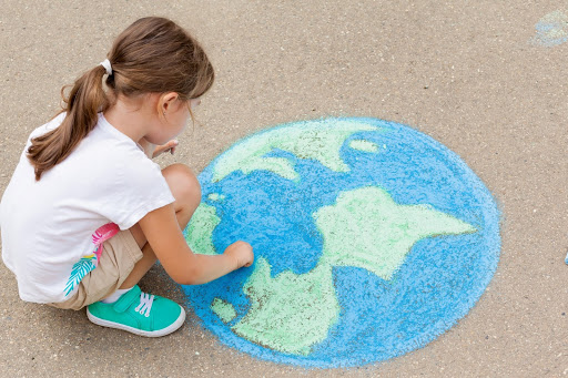 A small girl drawing a picture of the world on the sidewalk in blue and green chalk.