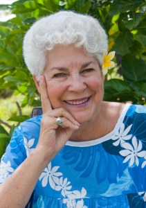 Picture of a lovely smiling woman in a blue and white Hawaiian blouse and a flower in her hair.