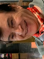smiling man with dark hair and and bright neck scarf