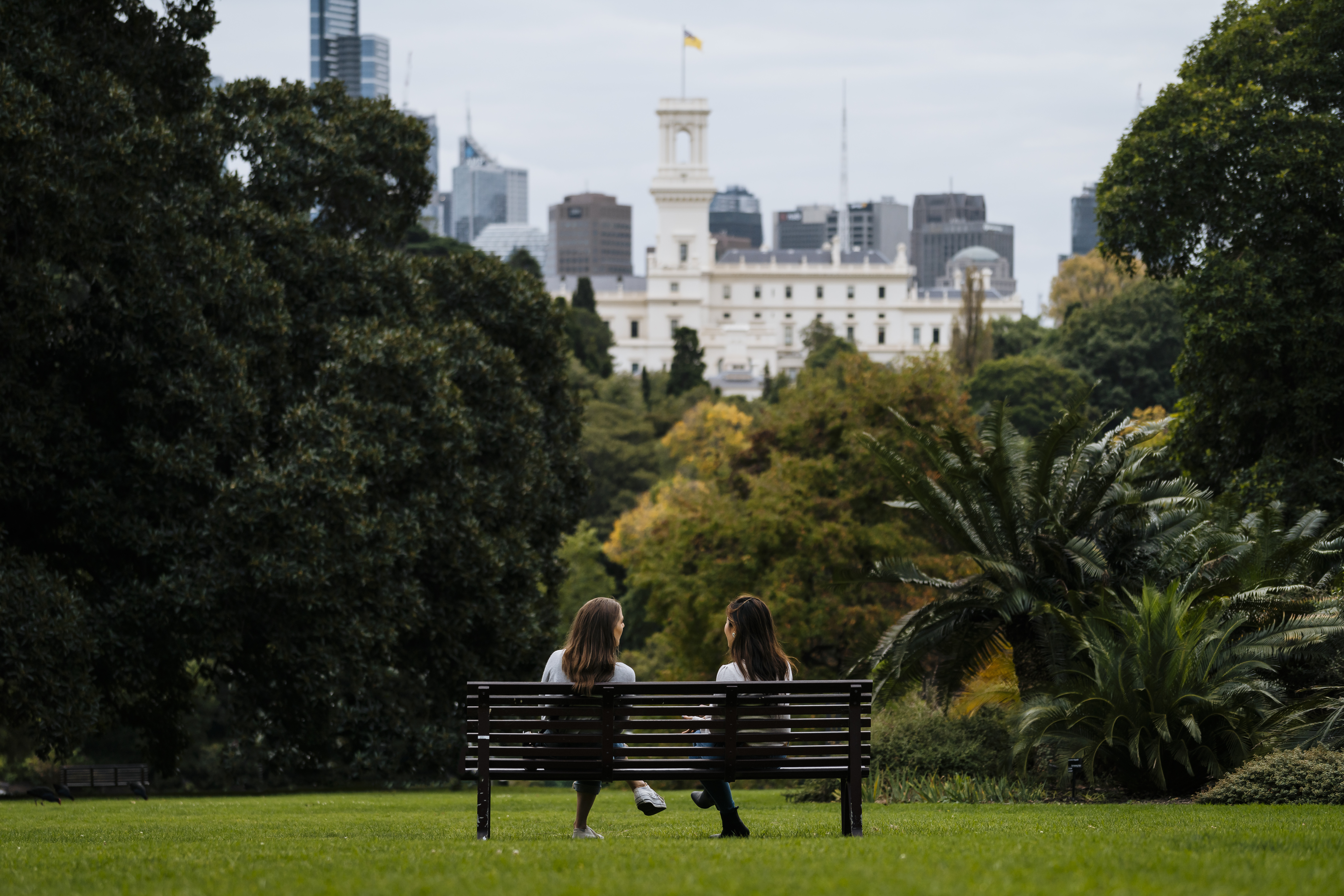 Two people sitting on a bench in Melbourne Royal Botanical Gardens with the CBD visible in the background.