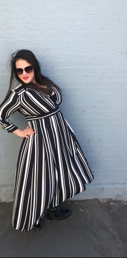 A brunette woman wearing sunglasses and red lipstick in a black and white striped dress in front of a blue brick wall.