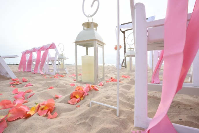 Aisle of sand with lanterns and sheppards hooks