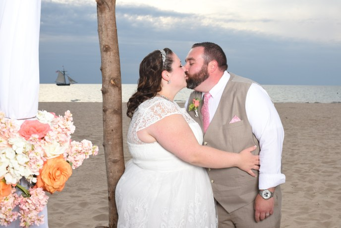 Newleyweds kissing with arbor and sailboat in background