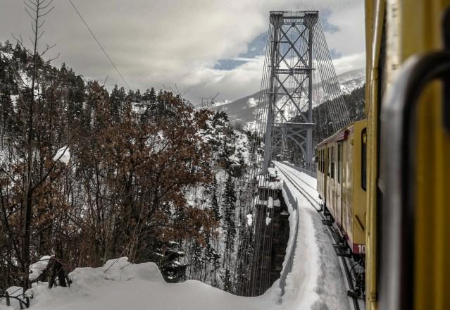 The Yellow Train, a french heritage, crossing a valley on the bridge of Cassagne, Pyrenees Orientales, region of southwest of France. Le Train jaune traverse une vallee sur le pont de Cassagne, Pyrenees Orientales, region du sud ouest de la France.