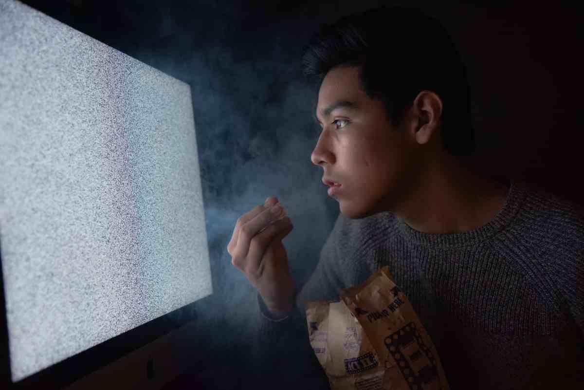 man eating chips while watching tv
