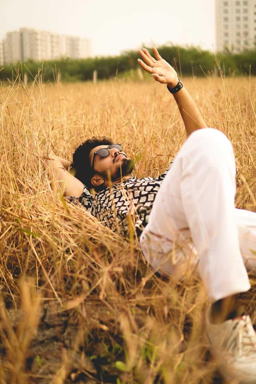 stylish calm man lying on grass in park