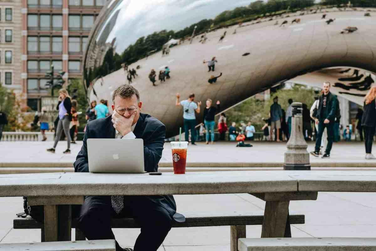 pensive businessman using laptop against cloud gate