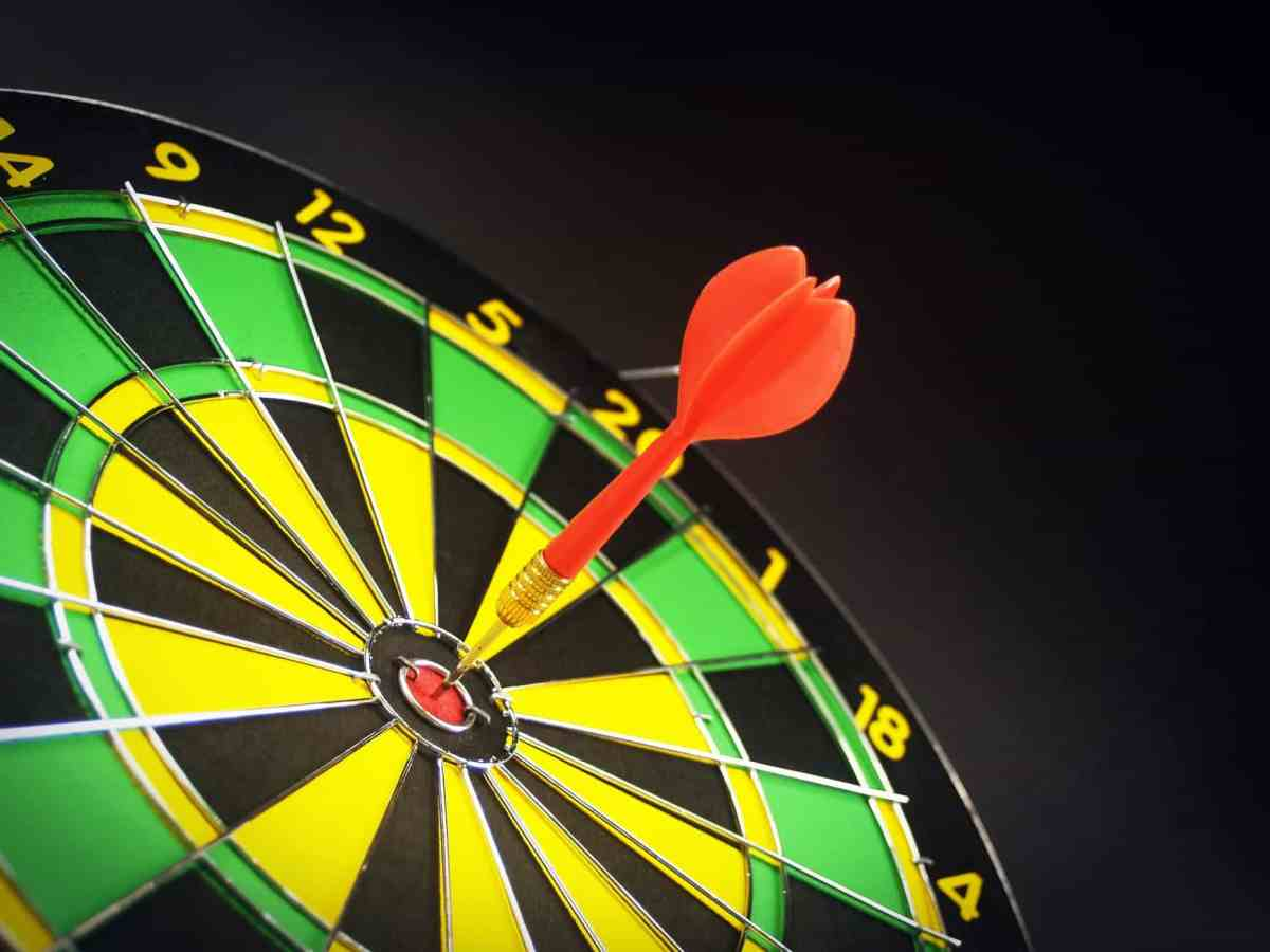 red and brass dart pin on dartboard