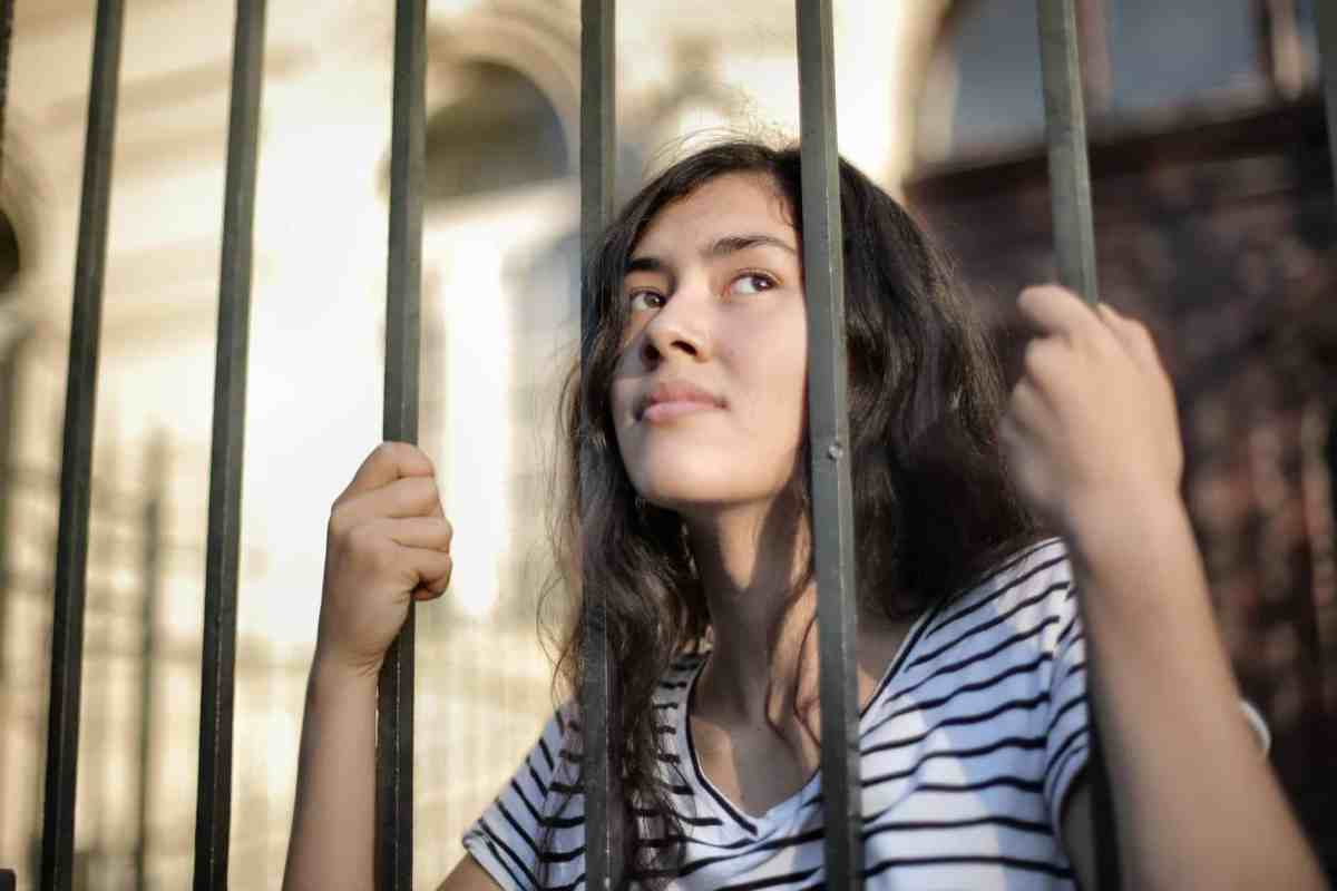 sad isolated young woman looking away through fence with hope - 4 steps to make change happen