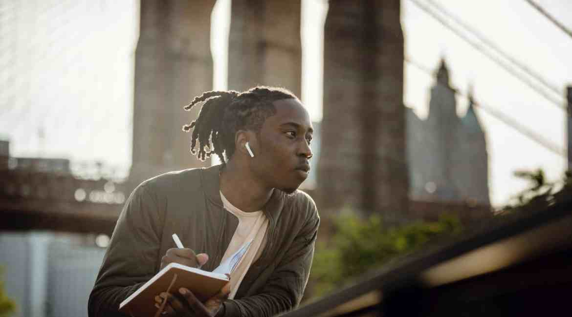 positive black man listening to music with wireless earphones and taking notes in diary on street
