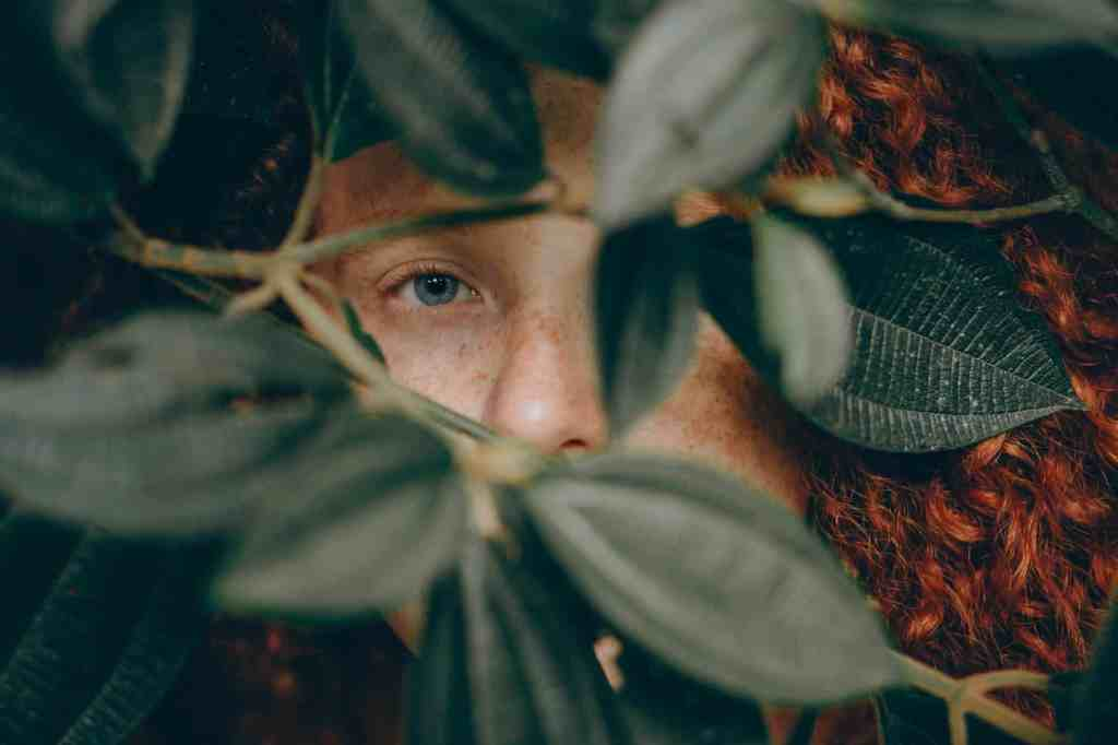 close up photo of person behind leaves