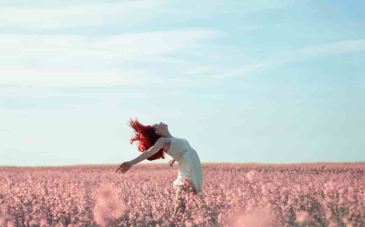 woman in yellow dress standing on pink petaled flower field - taking action is the only path to abundance