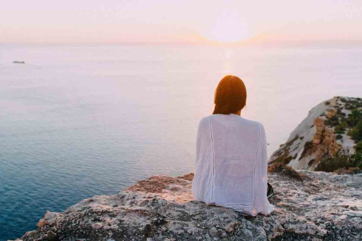 woman sitting on gray rock near body of water - power over your emotional state