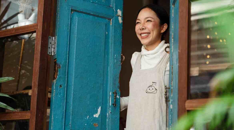 happy ethnic coffee shop owner standing at entrance door
