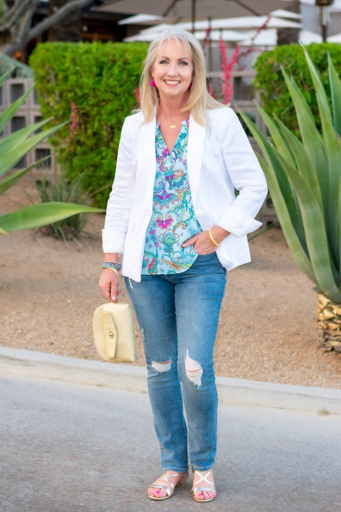 white blazer with distressed jeans and floral silk top