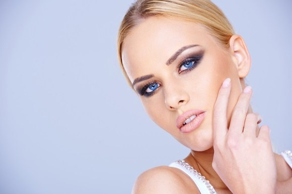 Beautiful blue-eyed blond woman wearing dark eye makeup looking at the camera close up head portrait