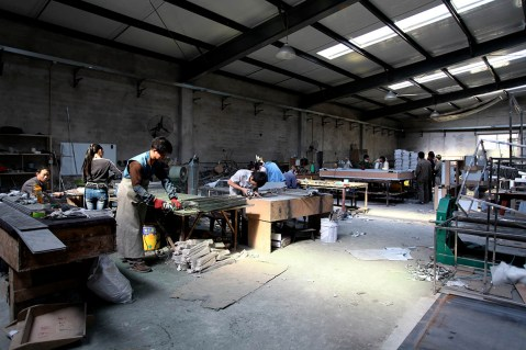 metal worker working corner inspecting control in Beijing factory   Leading Retail Renovation Brand – HTHY Group :: Photography of Factory for brand book