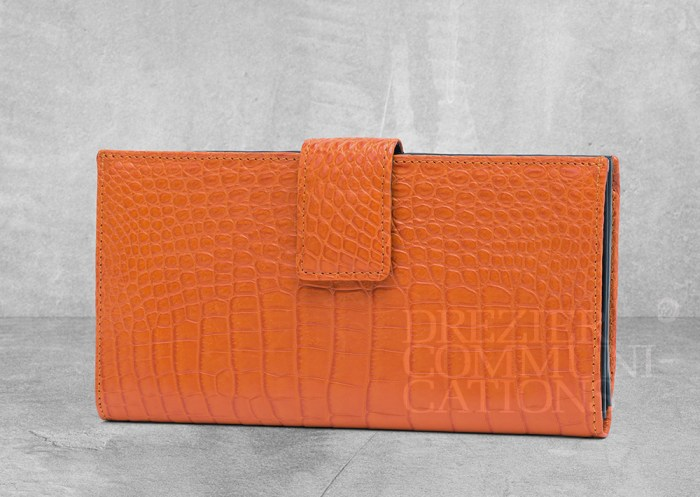 women's clutch bag orange stand up table top, accessories photography on cement background styling art direction retouched colour management | Garment Merchandising Company in Hong Kong : : Styling and Imaging of Apparel Made in and Imported from Italy Reselling through e-Commerce