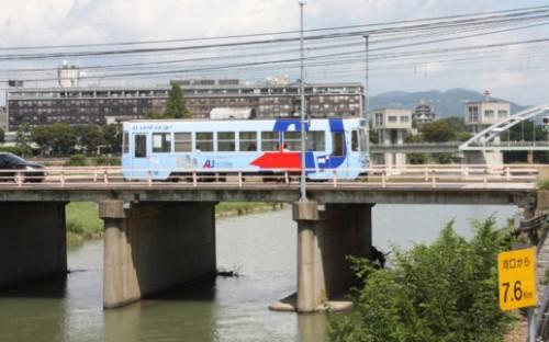 岡山城をバックに小橋を渡る7401号