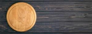 Empty Pizza Board on Dark Wooden Table.