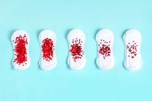 red glitter on menstrual pad - a period concept