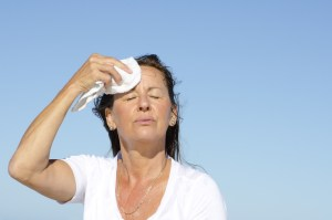 woman wiping her face with towel outside because she is hot