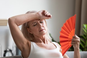 woman fanning herself due to menopause hot flashes