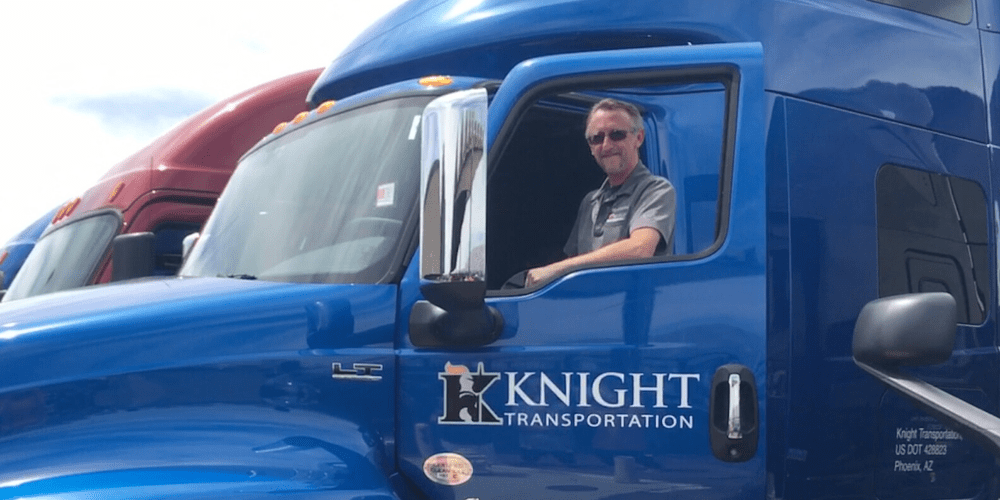 Driver standing in the door of his truck showing Knight Transportation logo