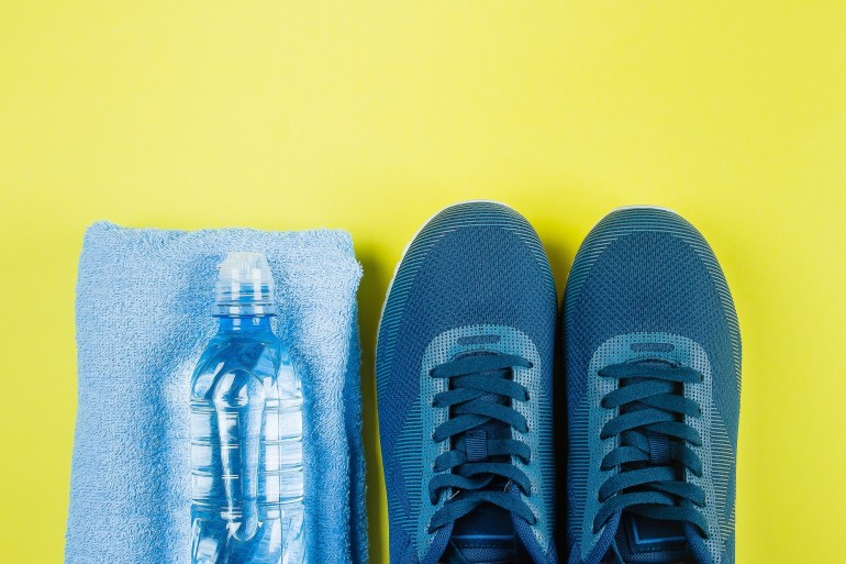 blue-sneakers-towel-and-water-bottle-on-yellow-background-sport-equipment-concept-of-healthy_t20_2w3ayE.jpg