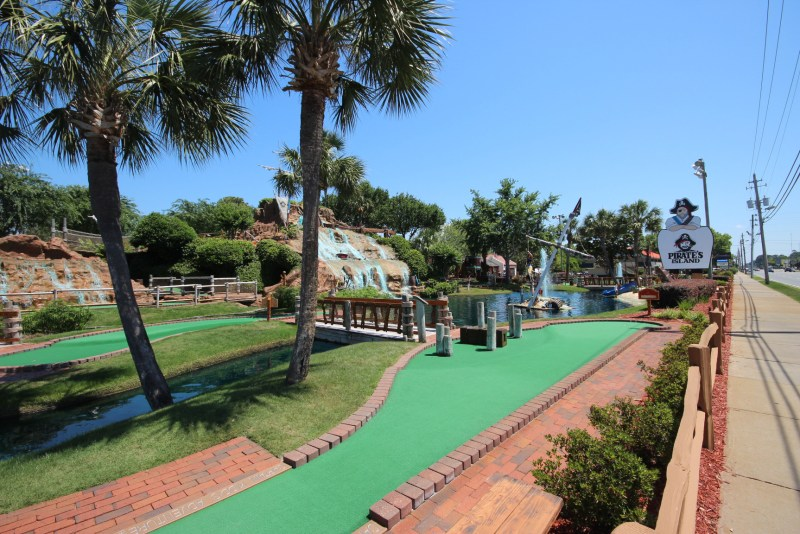 A well-manicured mini-golf green with trees and a waterfall in the background. Mini-Golf can be one of the more popular RV park amenities.