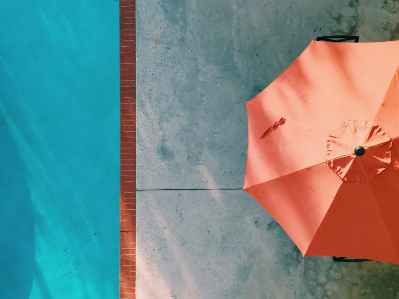 Top view of a partial swimming pool on the left and an orange patio umbrella on the right. Are swimming pools overrated?