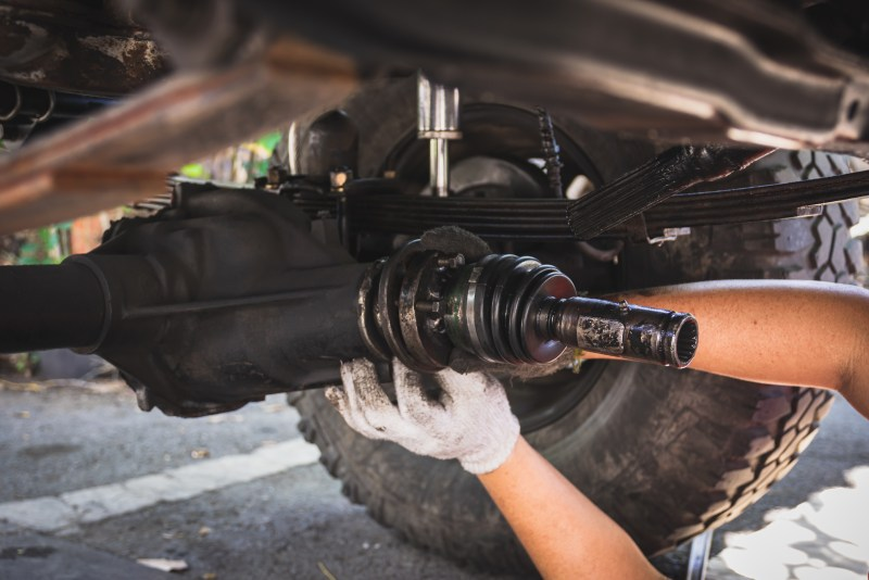 Hands repairing a front differential.
