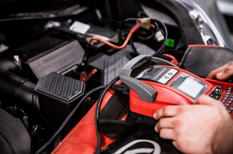 Mechanic testing battery on vehicle with device.