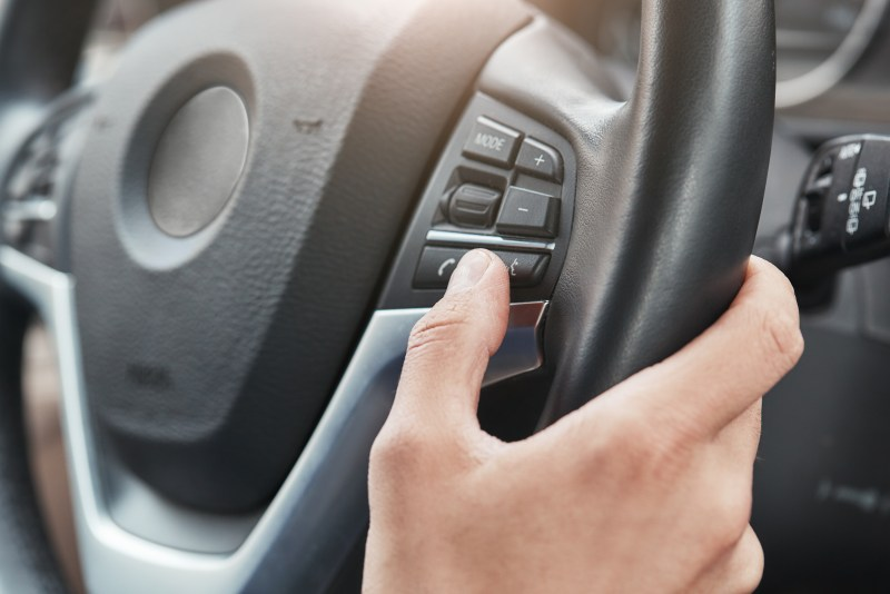 Person turning on cruise control on their steering wheel.