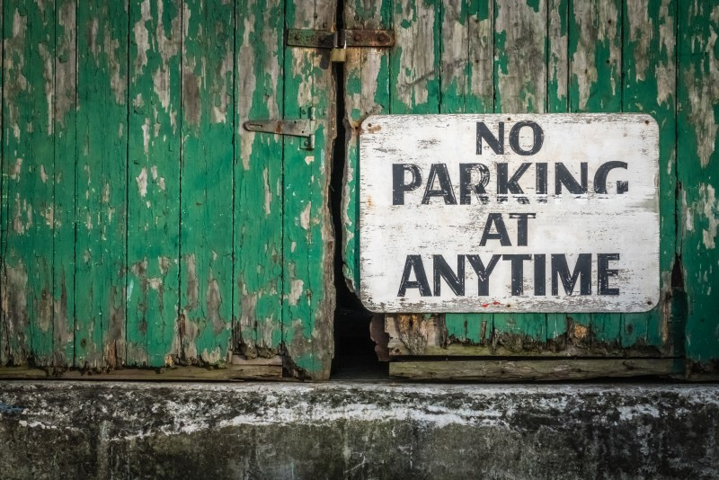 Sign attached to the old green wooden gates of a barrack stating that parking is not allowed at anytime