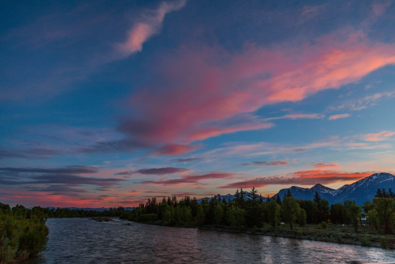 Sunset with pink and orange sky over scenic view of Jackson Hole.