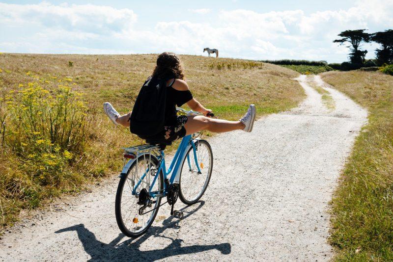 Woman riding bike on dirt road.