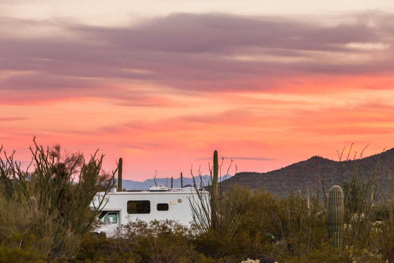 Small motorhome RV parked in the sunset