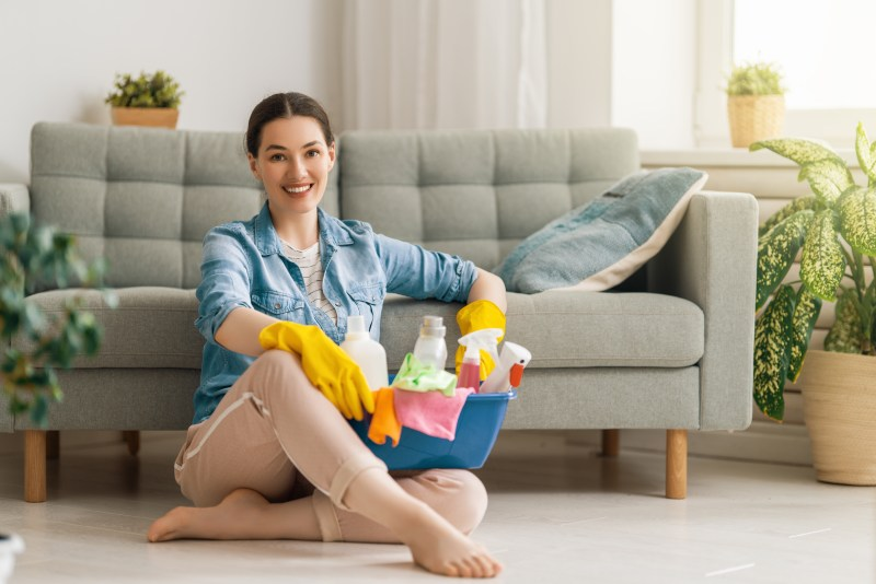 Woman sitting with a basket of cleaning products