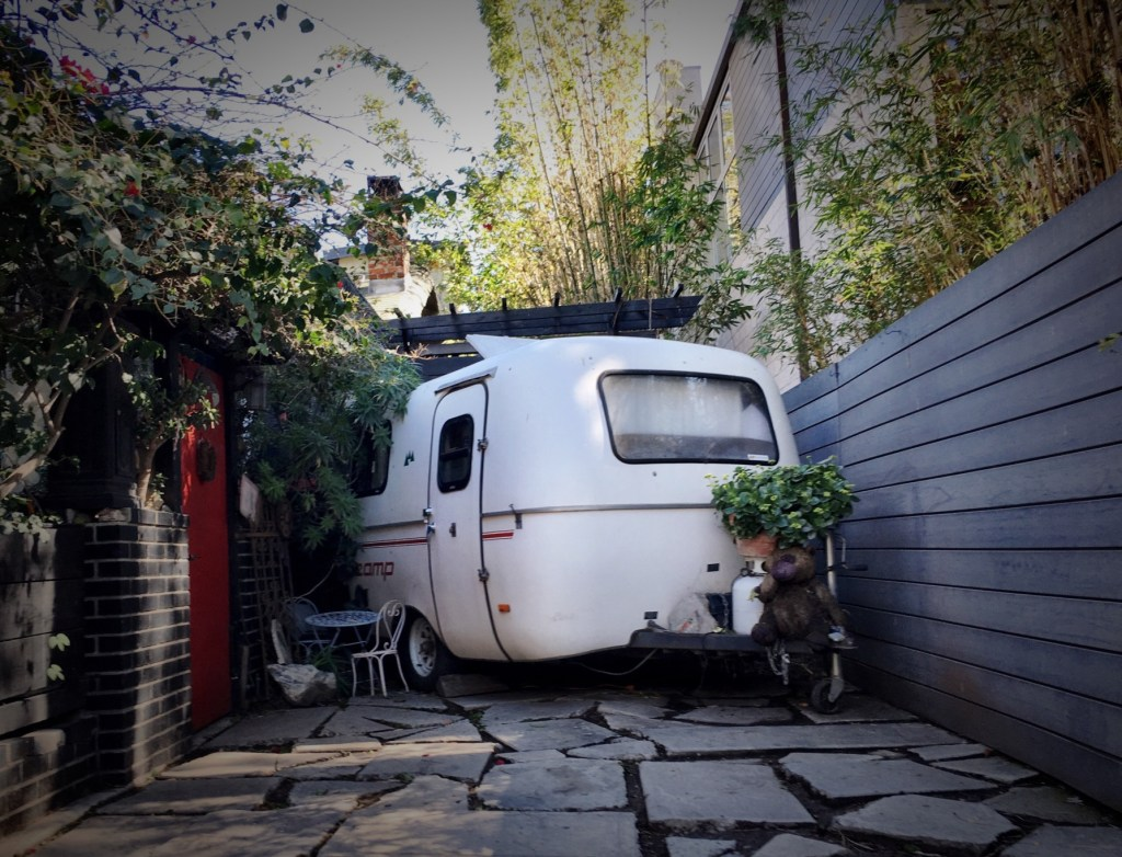 Small camper parked on a driveway.