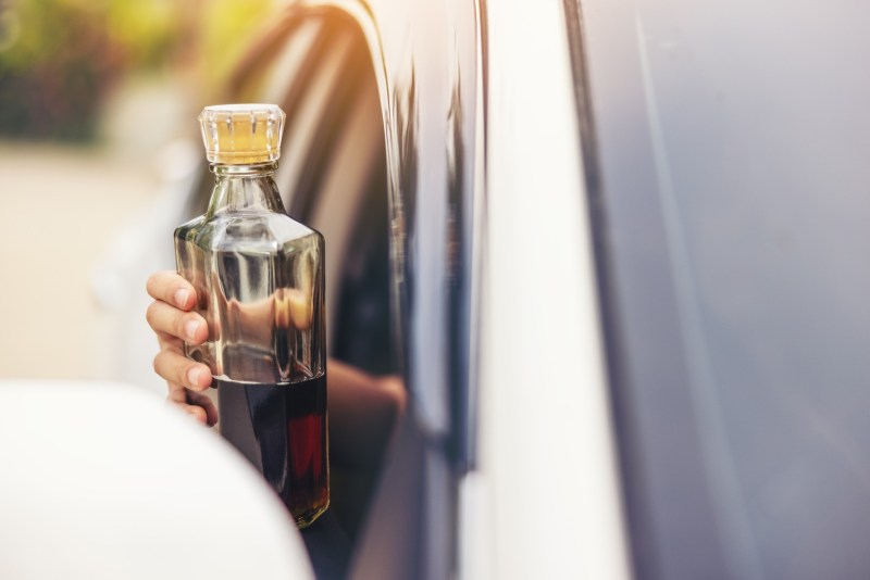 Woman hand holding a bottle of whiskey out of car window.
