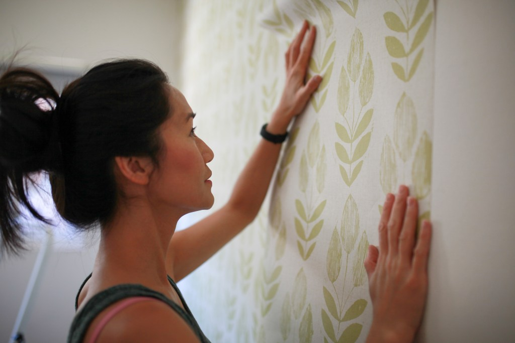 Woman hanging wall paper.