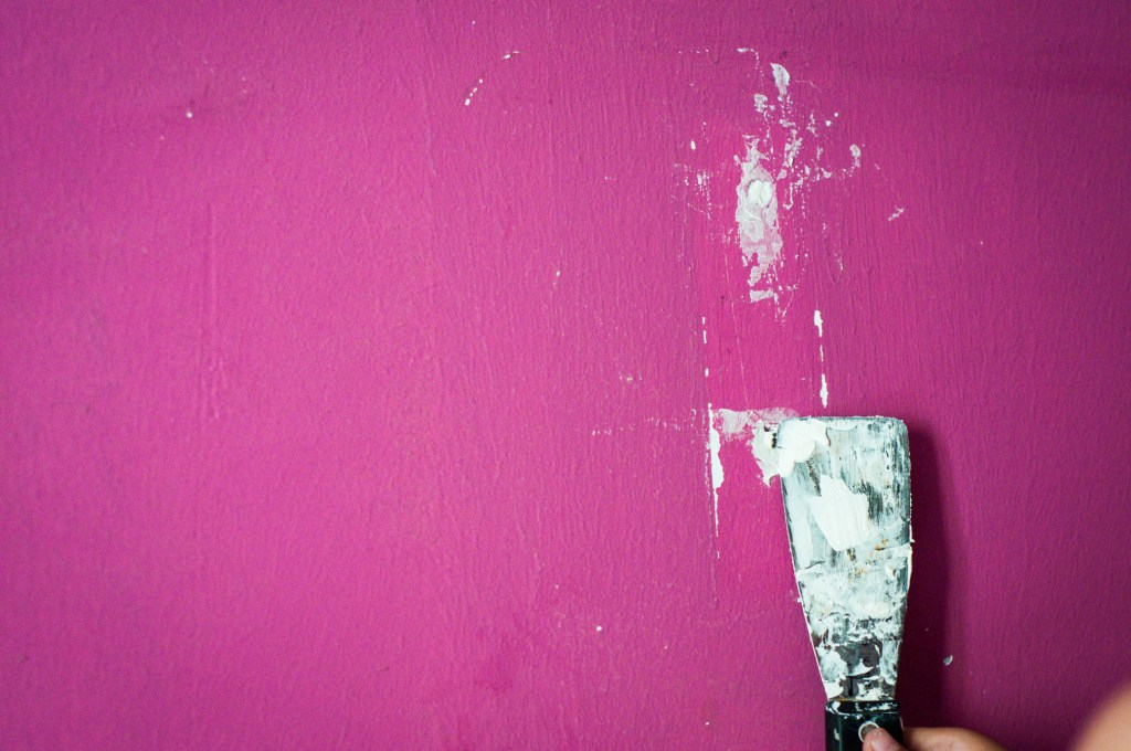Close up image of someone filling a hole in the wall.