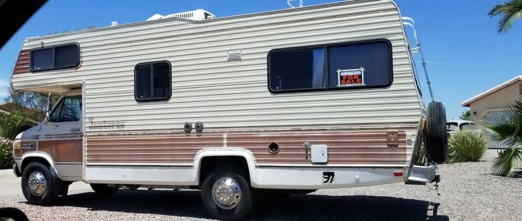 RV parked with a for sale sign.