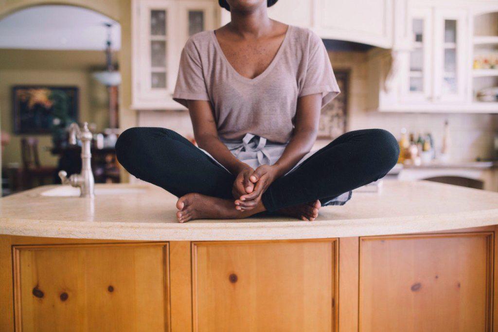 Woman sitting cross leg on counter top.