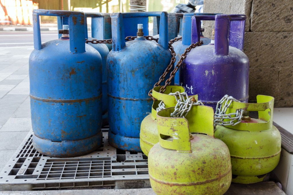 Different sizes and colors of propane tanks lines up.