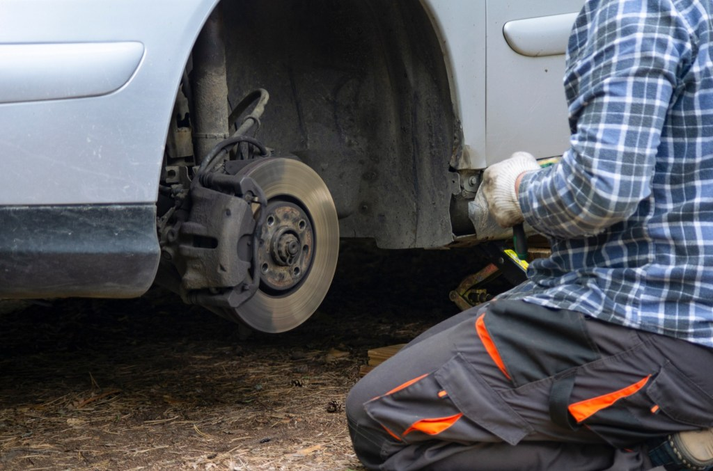 Man removing and rotating tires on his RV.
