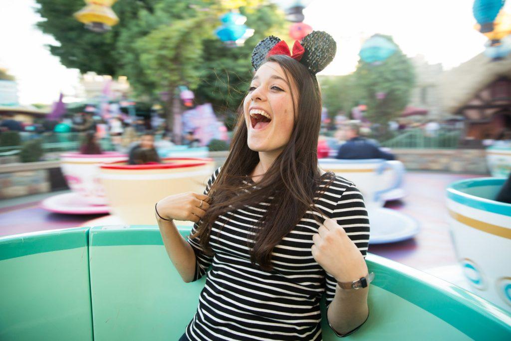 Woman riding magic teacups at disney.