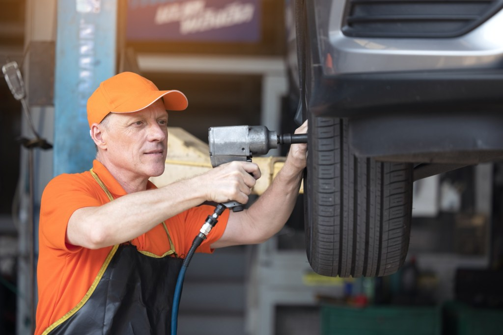 Male mechanic rotating a vehicles tires.