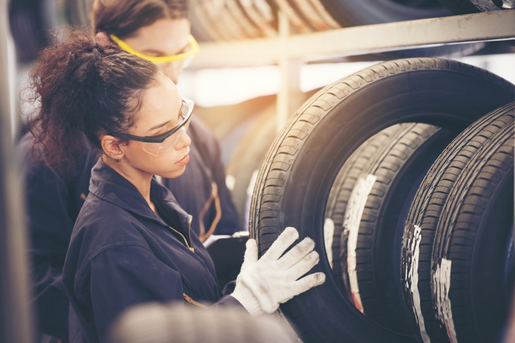 Woman mechanic picking out tire.